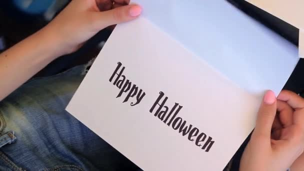 Dívka otevírá The Card. Happy Halloween napsaný v kartě