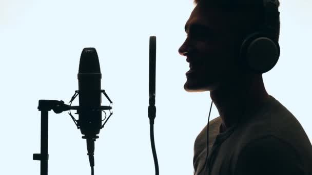 Handsome guy singing into a microphone standing backlit. Recording studio. Man silhouette.