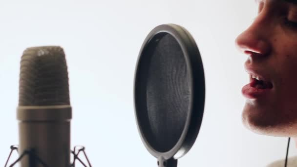 Cute singer recorded the song in a recording studio. The guy singing into a microphone. He stands on a white background. Backlight.