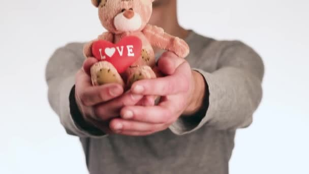 Cheerful guy gives a teddy bear and smiling. Bear paws holding a heart with the word love.