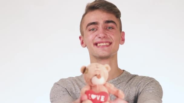 Handsome Guy Gives a Gift to His Girlfriend. In the hands of a guy toy teddy bear with a heart
