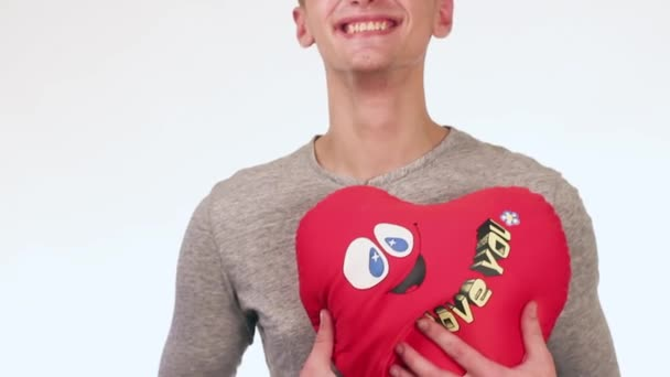 Handsome Guy Gives a Gift to His Girlfriend. In the hands of a guy toy teddy bear with a heart.