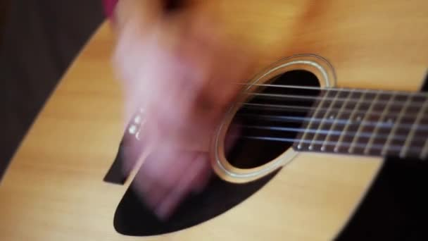 Musician playing on acoustic guitar. Close-up.