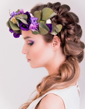Side view of a girl with flower crown posing in studio