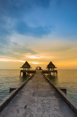 Walking way leading to lonely temple in ocean with beautiful natural sunset sky background