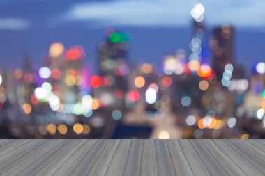 Wooden platform with abstract blurred bokeh city lights skyline