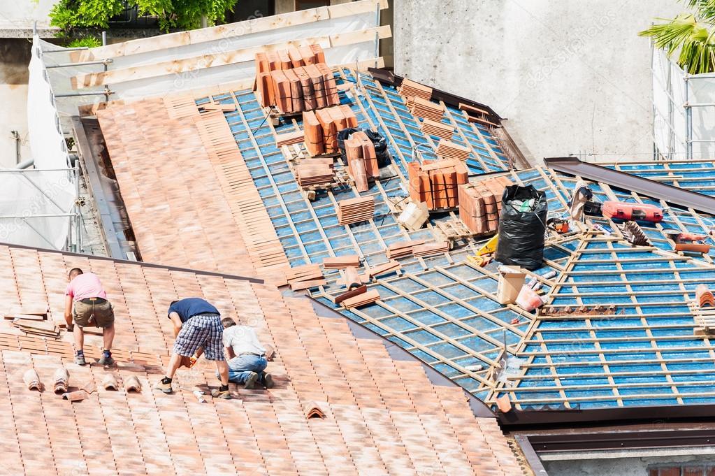 Muratori a lavorare sul tetto per la posa di piastrelle u foto