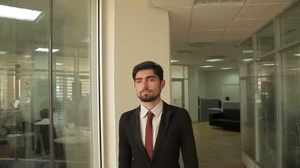 Atraktivní a sebevědomý podnikatel se procházel kolem moderní otevřený plán kancelářská budova.