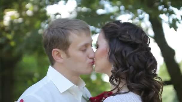 Nevěsta a ženich líbat a usmívá se na jejich svatební den