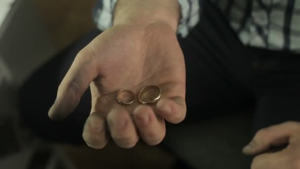 Man holding two wedding rings in his hands,  showing wedding ring to his bride