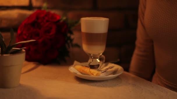 Žena pije kávu latte v kavárně