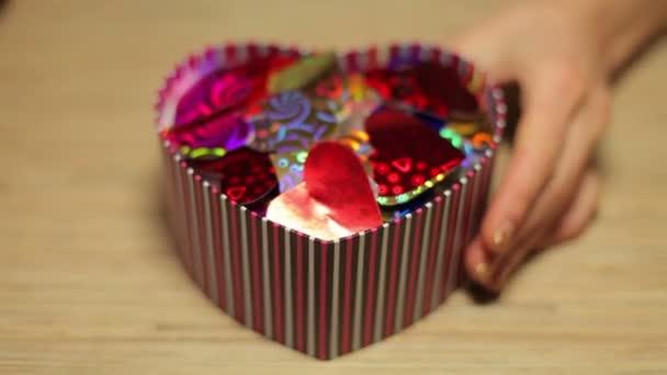 Ženské ruce otevřené krabice s dárek na Valentýna