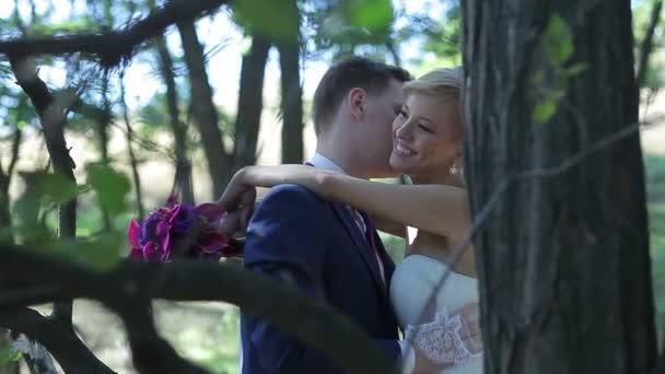 Nevěsta a ženich, mazlení, líbání a usmíval se na jejich svatební den v parku