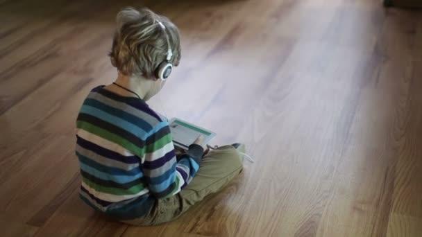 Chlapec poslouchat hudbu přes sluchátka pomocí počítače tablet Pc