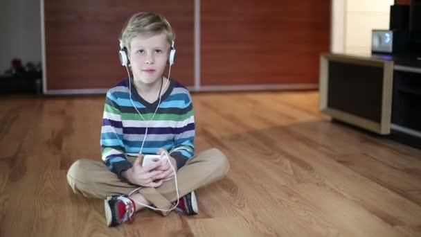 Fiú hallgató zene keresztül fejhallgató használ egy tabletta Pc