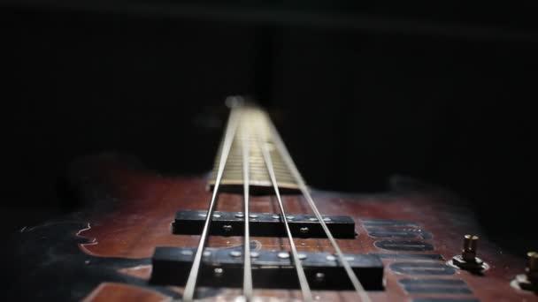 Basszus gitár húr rezgő. Közelről. Fekete háttér.
