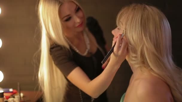 Makeup artist makes a girl beautiful makeup before an important event.  Woman applying cosmetic with a brush make up