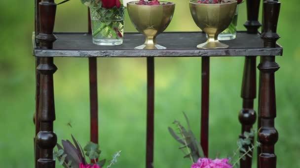 Na starožitné dřevěné stojí malá kytice růží a svatební dort