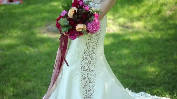 krásné svatební kytici květin v rukou mladé nevěsty. svatby. mladá žena v parku, lesa. Svatební oslavu. příroda, zelené pozadí