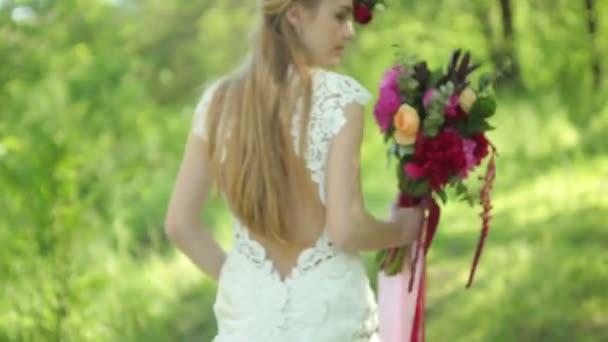svatební šaty s vlakem. krásné svatební kytici květin v rukou mladé nevěsty. svatby. mladá žena v parku, lesa. Svatební oslavu. přírodní zelené pozadí. životní styl pár rodina