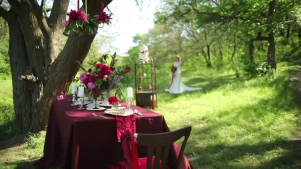 Outdoor Wedding table decorations and young bride with a beautiful wedding bouquet of flowers in hands