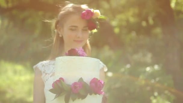 Beautiful bride holding a wedding cake with a flowers Outdoors