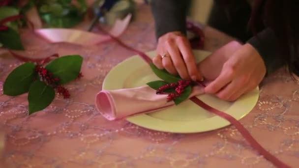 Female hands folding napkins. waiter folding napkin artistically with a flowers at restaurant table.
