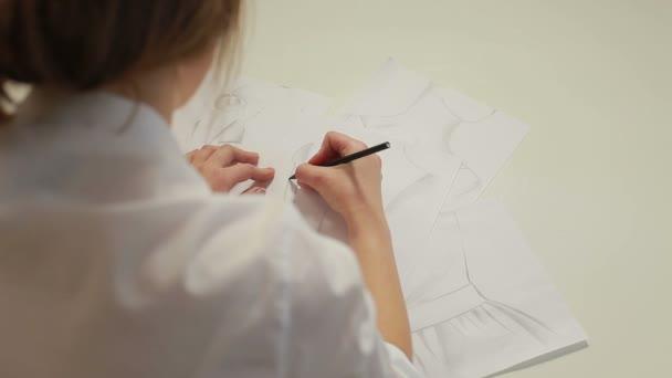 Weibliche Mode-Designer zeichnen Skizzen für Kleider im atelier ...