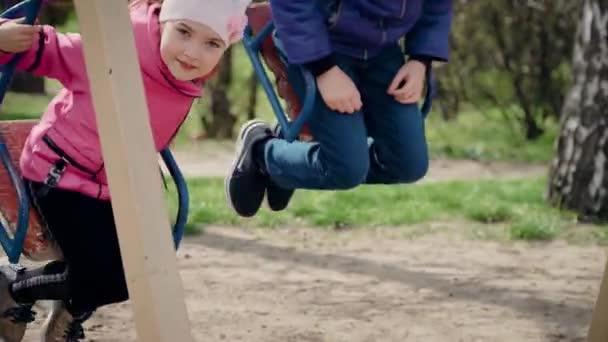 Kinder reiten auf Metallschaukel im Park. Süß mädchen und junge having spaß swinging zusammen im kindergarten
