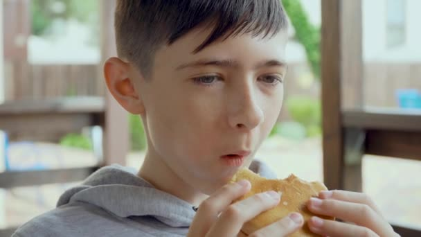 Cute teenage boy is appetizing eating fast food burger sitting in gazebo in front of house close up