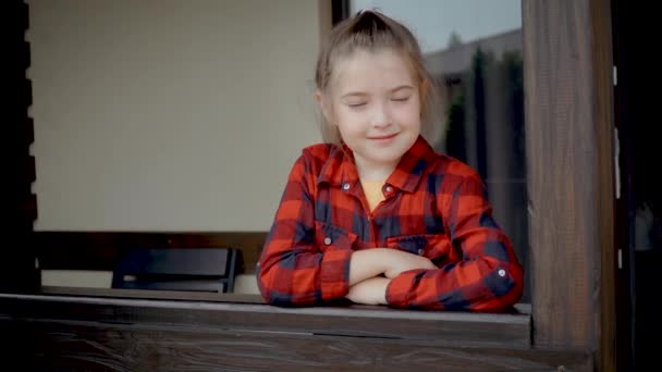 Close up portrait of serious little caucasian girl looking at camera. Adorable preschool kid standing it stands near house with wooden handrails