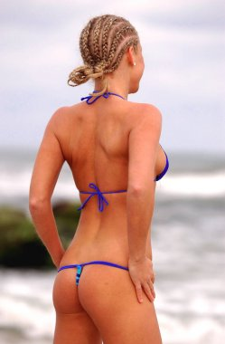Blonde beauty wearing unique swimsuit while posing on tropical island showing off her one butt cheeks backside rear end behind view of curved buttocks bottom