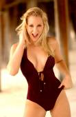 Photo Blonde goddess in one piece swimsuit playing with her hair while standing on the beach posing showing front side cleavage mouth open in laughter
