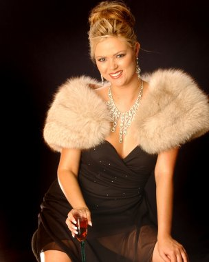 Sliver Necklace and Earrings Black Formal Dinner Dress Tan Fur Stole Elegant Blonde sitting down Drinking a Glass of pink wine getting ready to  of go out to fashionably affair