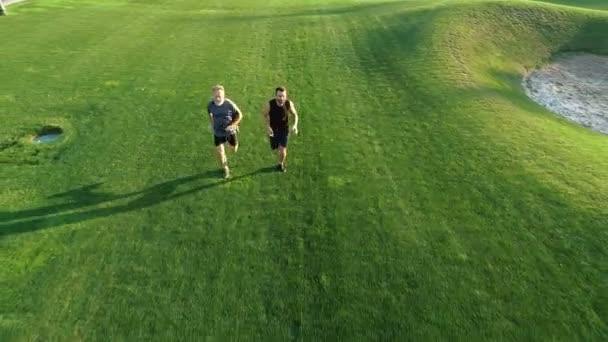 Dva muži běží na trávě v krásném parku