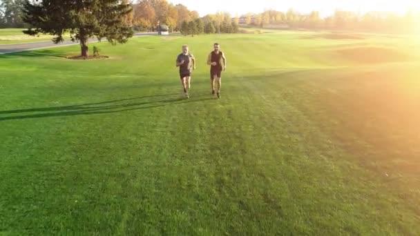Otec a syn běží po trávě v malebném parku