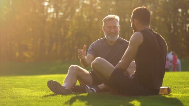 Der glückliche Vater und sein Sohn sitzen auf dem Gras und unterhalten sich. Zeitlupe