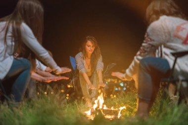 İnsanlar şenlik ateşinin yanında ellerini ısıtıyorlar. Akşam vakti.