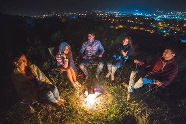 Beş arkadaş şenlik ateşinin yanında dinleniyor. Akşam vakti.
