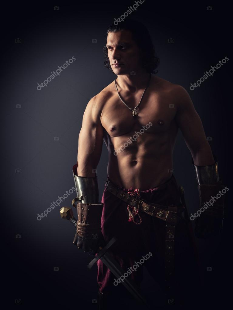 Half-naked warrior with a sword in medieval clothes