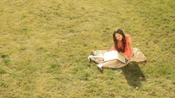 krásná holčička, sedět na trávě a napsal do svého deníku své sny