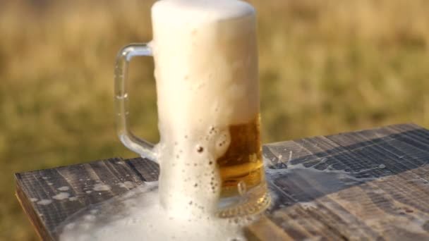 fresh beer is poured from the glass on a wooden table