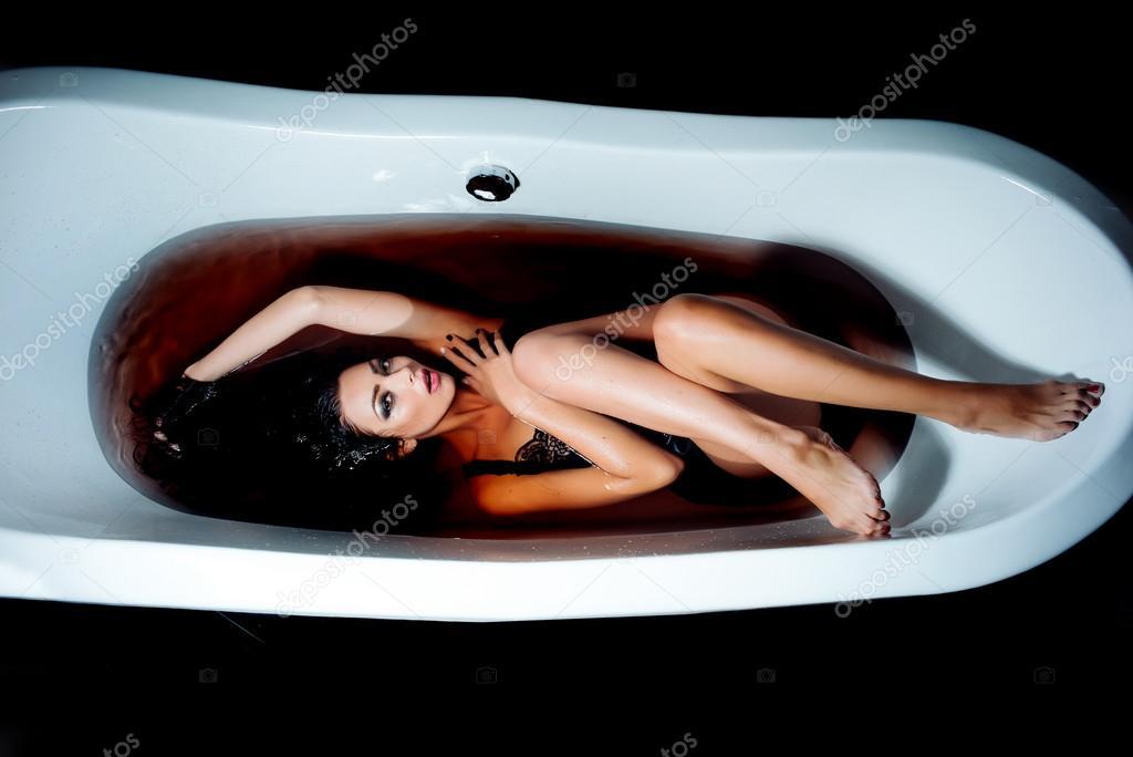 Sexy woman in dark bath water