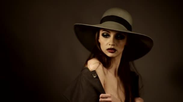 atraktivní dívka v klobouku s nahá ramena na focení v ateliéru