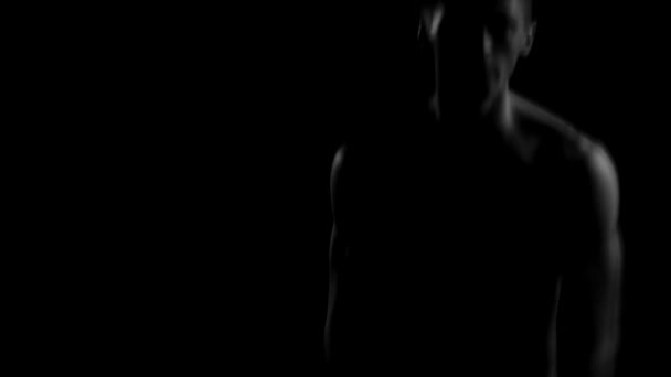 sexy naked guy with a nice athletic body dancing on a black background in the dark