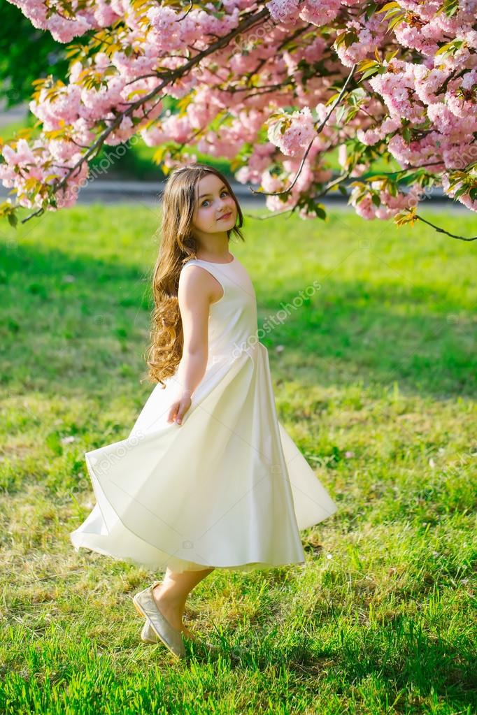 Beautiful small girl in white glamour dress with long hair and smiling face in spring pink flower blossom sunny day — Photo by ...
