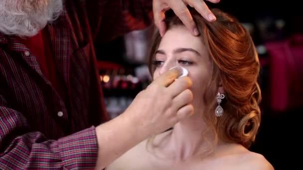 Maskérka čistí obličej krásné dívky s vatové tampony a krém před použitím kosmetiky a před make-up