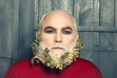 old man with flowers and leaves in beard
