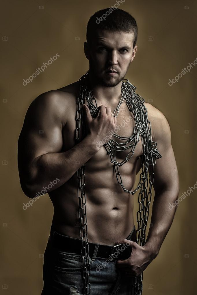 ae93e62206 Egy jóképű szexuális erős fiatalember, izmos test, kék farmer, gazdaság  kötél kézzel lóg a nyak és a vállak állandó pózol a sárga háttérrel,  függőleges kép ...