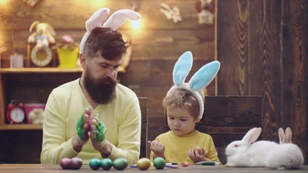 Happy easter family at home. Father and son wearing bunny ears, having fun paint and decorate eggs for holiday. White pet rabbit.